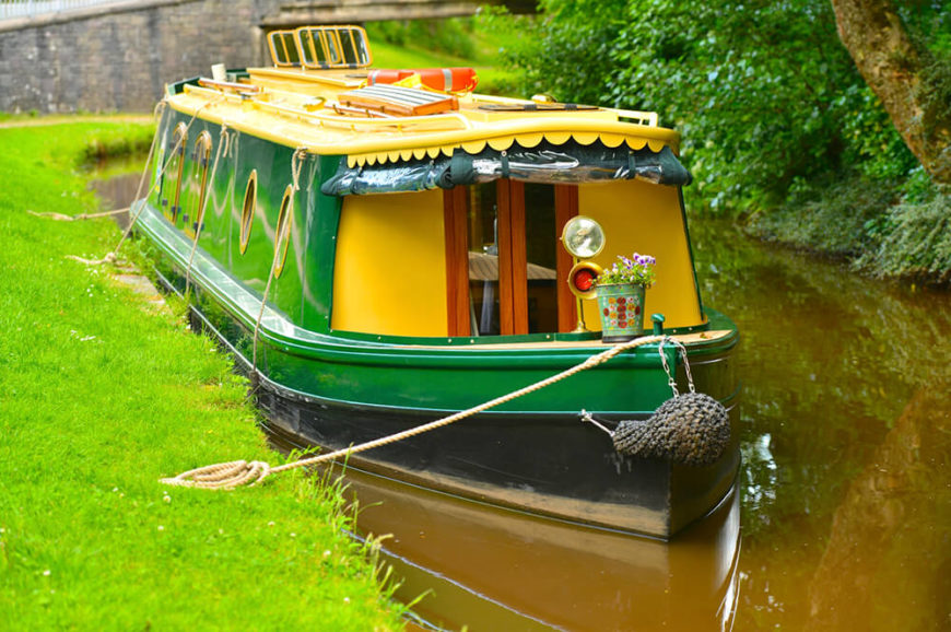 A brightly colored quaint houseboat with no open air deck. The boat is perfect for maneuvering through the canals of the Netherlands.