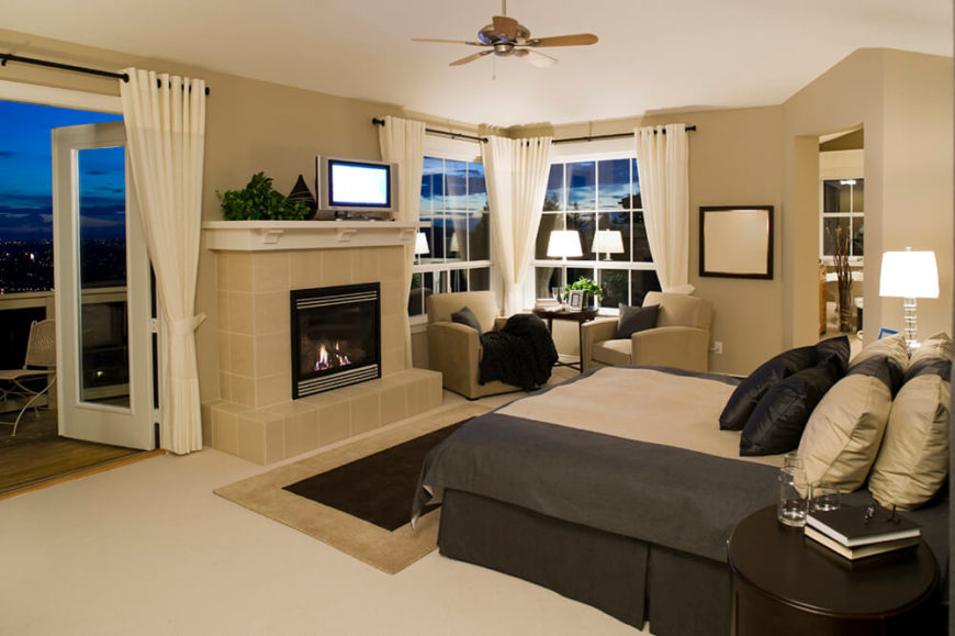 this master bedroom en suite features doorless bathroom access plus large windows and a set of