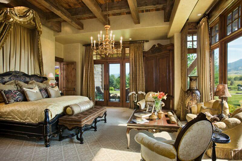 This immaculately dressed bedroom features rustic touches like exposed wood beams in an ultra-luxurious style. In addition to massive windows, the room boasts a set of wood framed, glass French doors for patio access.