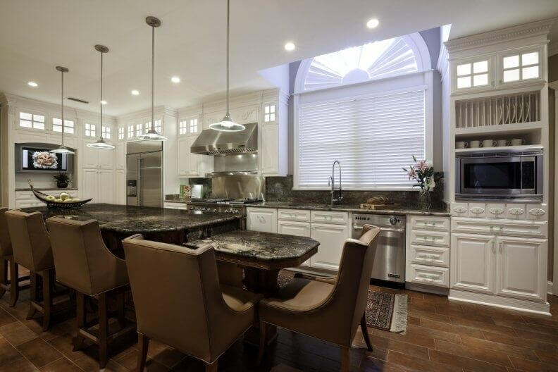 Stately Leather Chairs Add Class And Color To This Bright White Kitchen While Dark Granite Counters