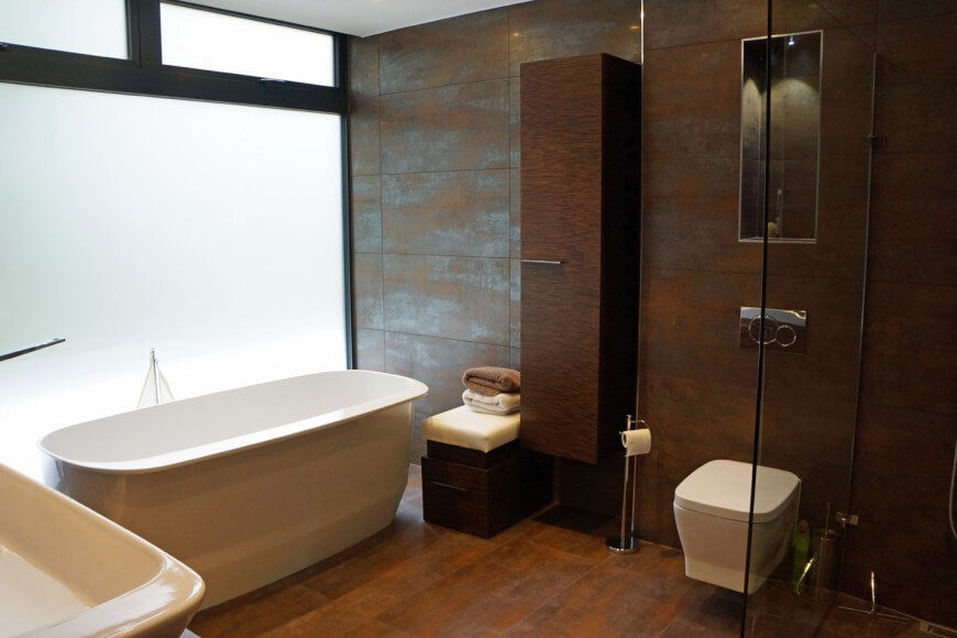 A Spacious Bathroom In Rich Browns, Featuring Large Format Tile With A  Slight Metallic Sheen