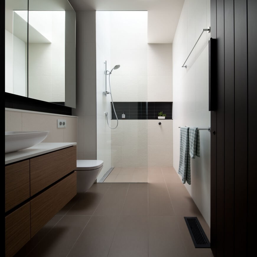A modern bathroom with a bit of Asian design flair  featuring an open  shower partially. 35 Enviable Master Bathrooms By Popular Designers