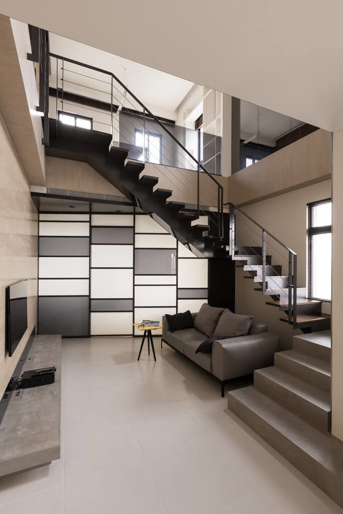 Resting in a unique position, situated at the bottom of a vast stairwell void, this bespoke living room showcases the minimalist aesthetic perfectly. A single leather sofa and small wood table sit across large format tile flooring from a slim media shelf and wall mounted television.