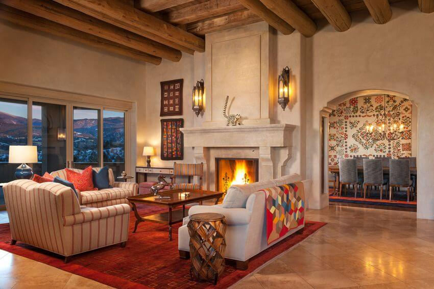 Luxury can take all sorts of forms. Here we've got a safari-themed space that pairs rich marble flooring with rustic exposed wood ceiling beams, sandwiching a space centered around a massive fireplace. The furniture centers on a red area rug, basking in the light from sconces and the large glass panels at left.