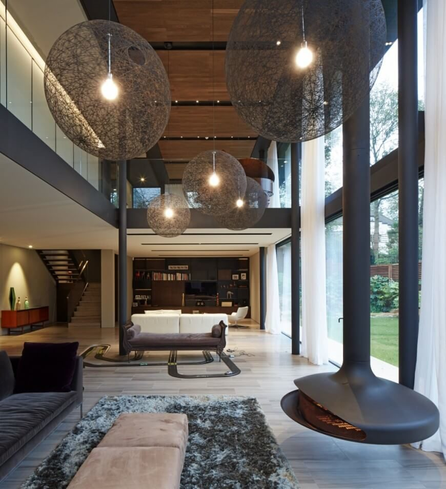 In a vast open plan space towering over two stories tall, a series of large spherical chandeliers hang filling the air space over contemporary furnishings. The hardwood floor expands toward a bespoke media room at the far end, while a pair of dark sofas and a hanging fireplace fill out the foreground.