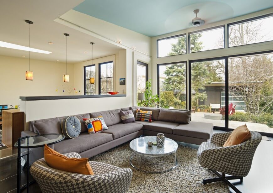 The high ceiling and massive windows allow this living room to feel vast and open, with tons of natural light pouring in. A modern sectional is paired with a glass coffee table and pair of houndstooth-print club chairs at center.