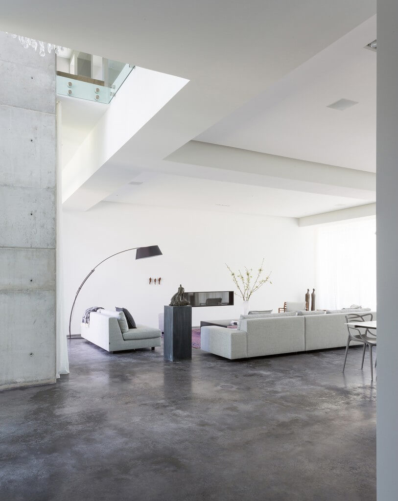 Here's another fantastic case of less-is-more style informing a large, modern living room. The bespoke contemporary sofa sections are placed within a vast open area, centered on a discreet purple rug and gas fireplace mounted within the wall, making for a self contained comfort zone amidst the expanse of cool concrete flooring.