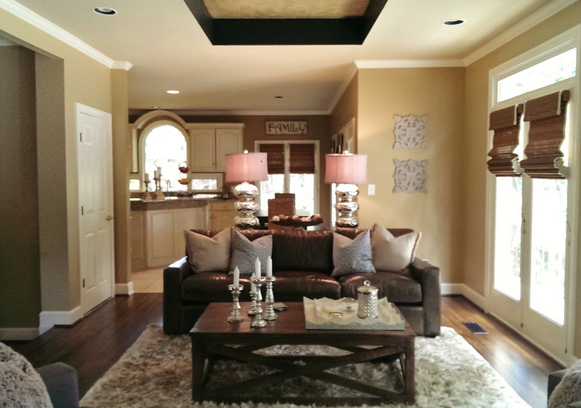 We love seeing traditional style meeting modern luxury in a cozy setting; these less ambitious but equally beautiful living rooms feel close to home. The dark chocolate hued leather sofa and natural wood coffee table stand on a thick area rug over hardwood flooring in a home with an open plan layout.