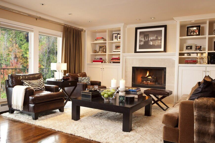 The marble fireplace at the center of this room is flanked by sets of built-in cabinetry and shelving, all overlooking a set of comfortable contemporary furniture. The large dark wood coffee table is paired with plush leather armchairs at left and a light brown sofa at right.
