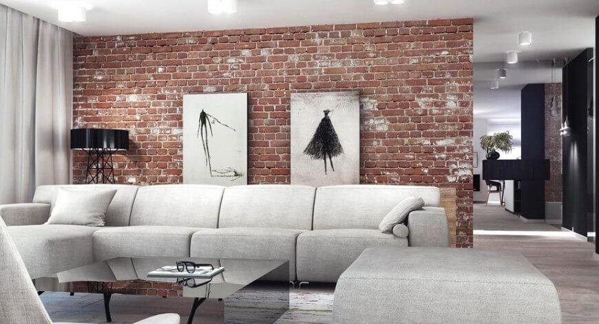 We love the mixture of industrial style brick and sleek hardwood flooring in this contemporary home. Thick padded light grey sectionals wrap a monolith-like black coffee table for a burst of contrast.