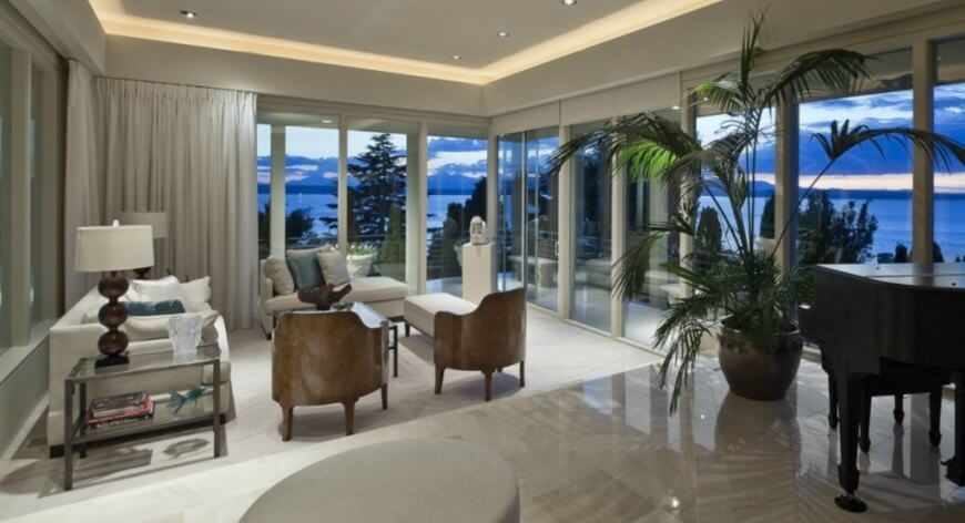 Wraparound glass grants this luxurious living room an expansive feeling, as does the polished marble flooring. The slim set of furniture sits off to one side, comforted by a tight gathering of wood club chairs and white upholstered sofas.