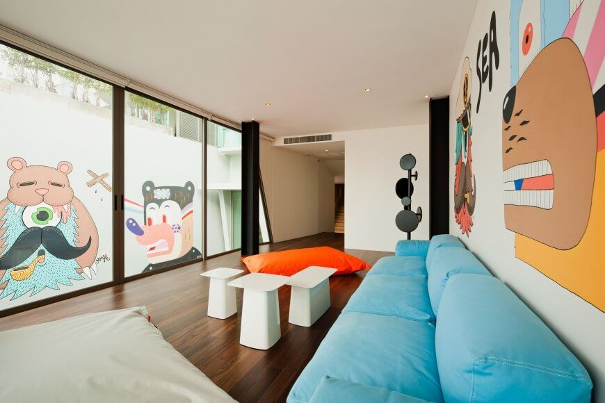 We love seeing contemporary art in modern homes, and this sleek, minimalist living room is filled with bright imagery on both interior and exterior walls. The sky blue sofa is complemented by a bold orange beanbag chair, as well as the high contrast between dark hardwood flooring and white walls.