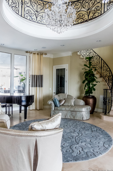 This ornate living room sits beneath an open two-story tall void where a catwalk circles the chandelier, a truly unique visual statement. The luxuriously styled furniture centers on a detailed area rug, with a grand piano sparkling in sunlight, courtesy of full height windows.