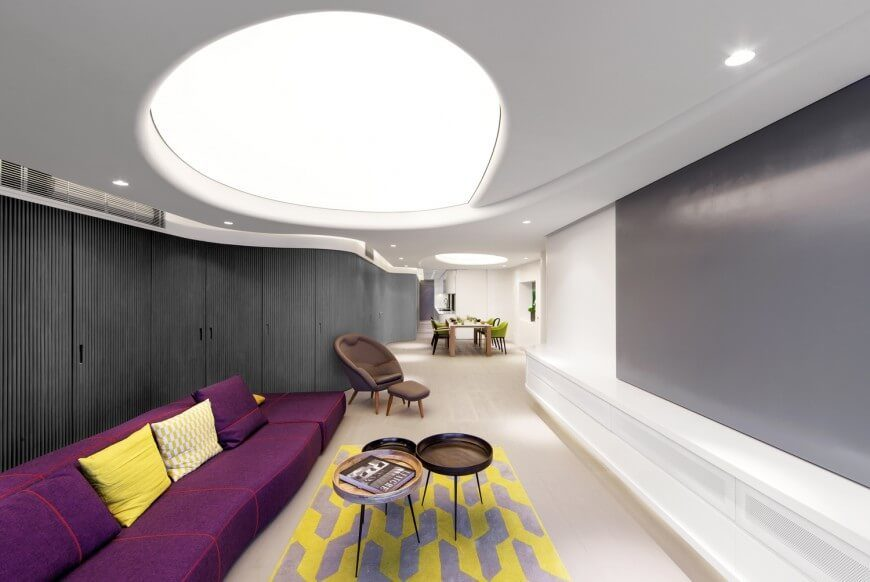 In a super-sleek, ultra modern space informed by strict minimalism, we see the bright flash of purple and yellow courtesy of the sectional and rug combination in the foreground. This contrasts nicely with the understated white and grey color scheme of the home.