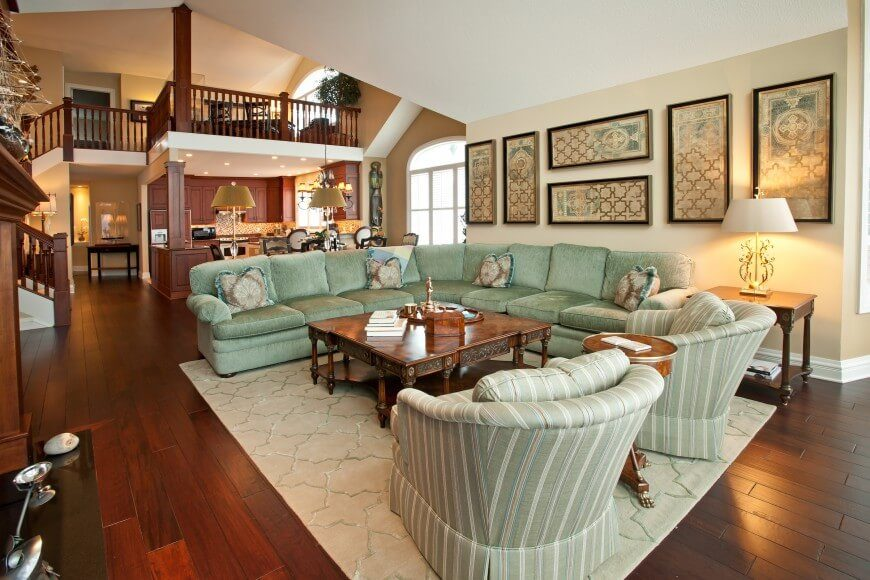 This living room is part of a larger open-plan area within the home, defined by a massive wraparound sectional in mint green. The ornately carved wood coffee table offers contrast, and helps connect the room to the wood filled rest of the home.