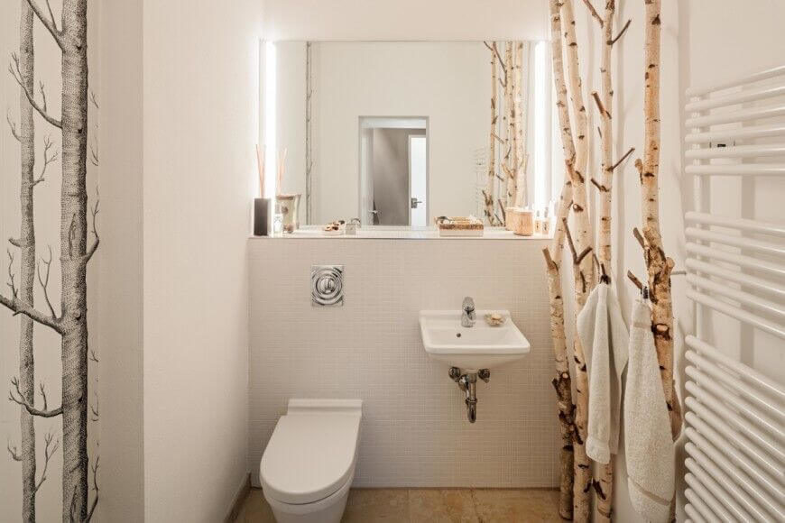 This unique space is accented by the thin birch trees standing to the side of the sink and opposite of the shower, These limbs act as both accents for the room as well as hangers for towels and clothing. Adjacent to these is a floating sink and large mirror, with a toilet directly next to the sink.
