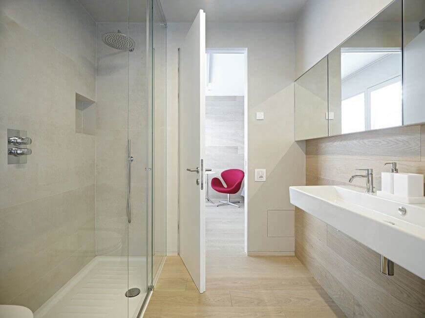 A modern style bathroom, this space features a light hardwood floor, which runs halfway up the wall and ends just below the mirrored cabinets. A long floating sink is featured just below the cabinetry, while a glass wall shower is featured on the opposite side of the room.