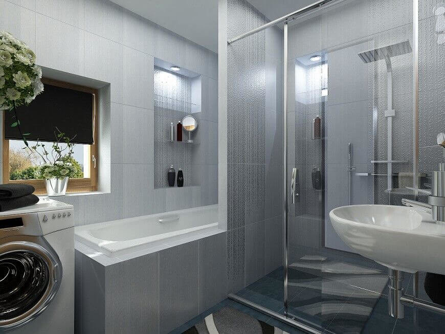 This bathroom shares a space with a washer and dryer, but there is still plenty of room to move around comfortably. Large grey tiles cover the walls and create a futuristic feel for the room. Notice the corner of a stylish carpet covering the floor. The bath and shower are taking up a large space, but their positioning helps to conserve area in the bathroom.