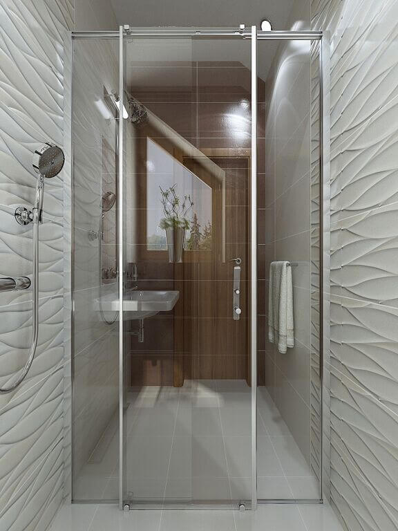 This angle reveals a view from inside the shower. You will notice a wavy pattern on the interior of the shower, while outside of this space the material transitions into grey tile. There is a floating sink located on the left, and a small doorway on the right of the far wall.