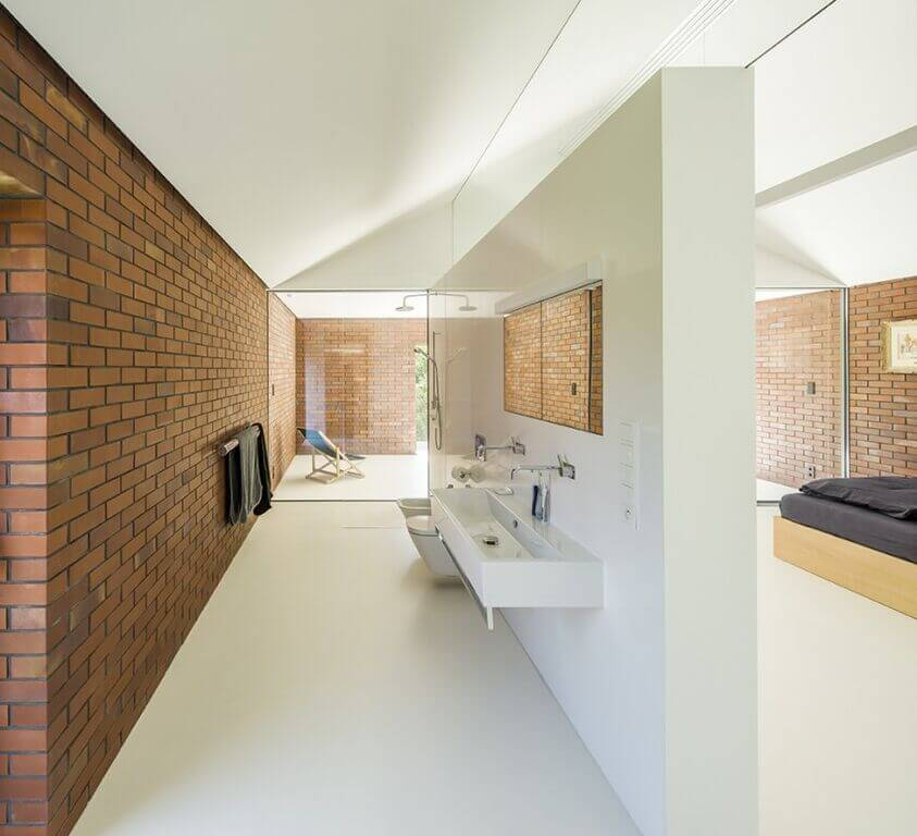 This bathroom takes up a large space, with a large white wall separating the bathroom area from the bedroom. While the walls consist of a traditional red brick, the floors and separating wall are stark white, providing a healthy balance for the space. A trough style floating sink is featured on the inside of the separation wall, as well as a glass walled shower on the far end.