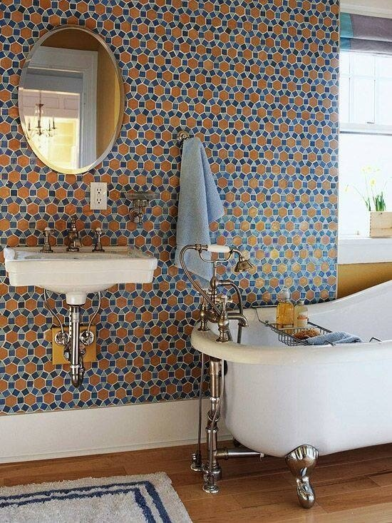 This bathroom features a wall covered in tile that forms a unique pattern. The blues and brown color works together to contribute to a calming atmosphere, white the clawfoot tub and floating sink add classical appeal. There is a large window near the head of the tub, which lets in light for the room.