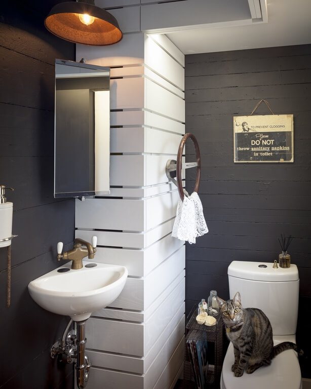 A small space holds a toilet, and floating sink, and corner mounted mirror. An accent wall takes up the corner space, and features a steering wheel decoration that doubles as a place to hang hand towels. The dark walls help to contrast the white utilities and white accent wall.