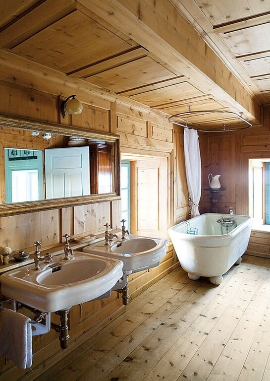 Natural wood fills this bathroom, covering the floor, the walls, and the ceiling. A clawfoot tub is featured in the corner between two windows. Directly to the left of the tub and window are two floating sinks sharing one large mirror.