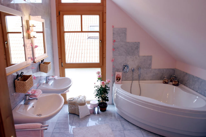 The angled ceiling makes this bathroom a cozy small space. The tub is tucked in the smallest corner of the room with tiles running along the perimeter of the bath and faucet, serving as a backsplash. A window with frosted glass panes on both the top and bottom sides allow for natural light to fill the room. Two small floating sinks are featured.