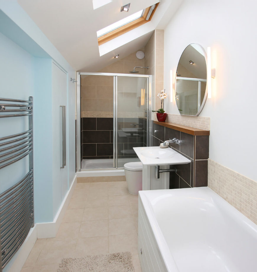This bathroom features a section of large dark tile behind the sink and in the lower half of the shower. The small square tile backsplash runs along the wall behind the tub, as well as above the sink and in a vein through the middle of the shower. A slanted ceiling features a skylight, which helps to keep the space bright.