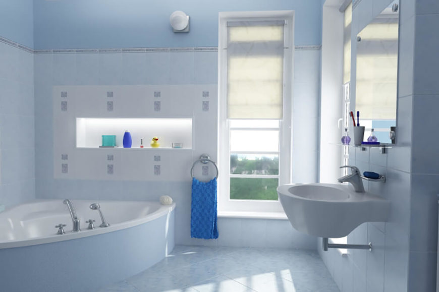 This bathroom features a light blue textured tile floor, and the tile runs up the entirety of the wall up to just below the ceiling. A floating sink hangs below a mirror with a small shelf for toiletries. There is a large corner tub, with a shelf just above the tub for storing toiletries and other decoration.