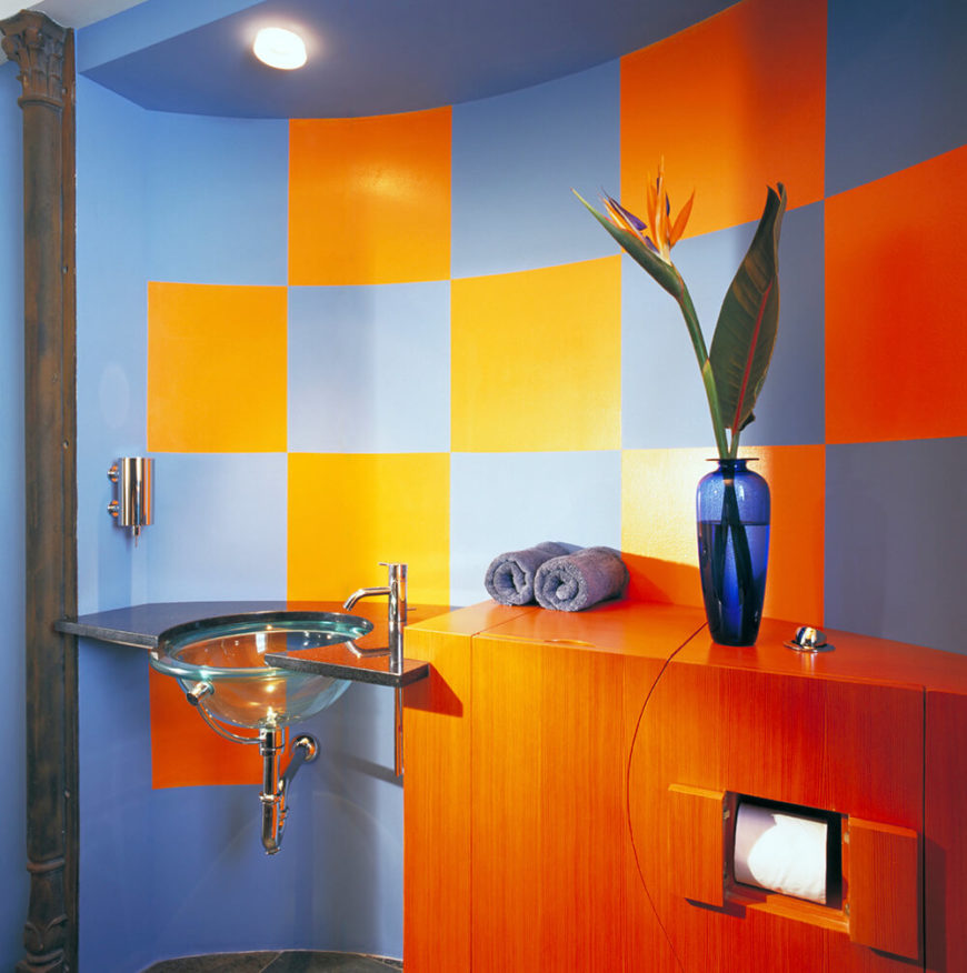 This bathroom has a bright and vibrant color scheme, with a checkered pattern on the wall behind the sink and counter. The unique counter space has various openings that reveal commodities like toilet paper, but they can also be hidden if necessary. The floating sink has a unique transparent glass structure.