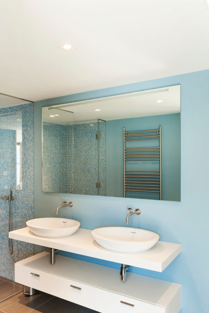 Small square blue tiles cover the interior of the shower, while the walls transition to a solid baby blue behind the sinks and mirror. Beneath the floating sinks there is a set of white drawers that provide plenty of storage space. In the reflection of the mirror, you can see a chrome towel rack on the opposite wall.
