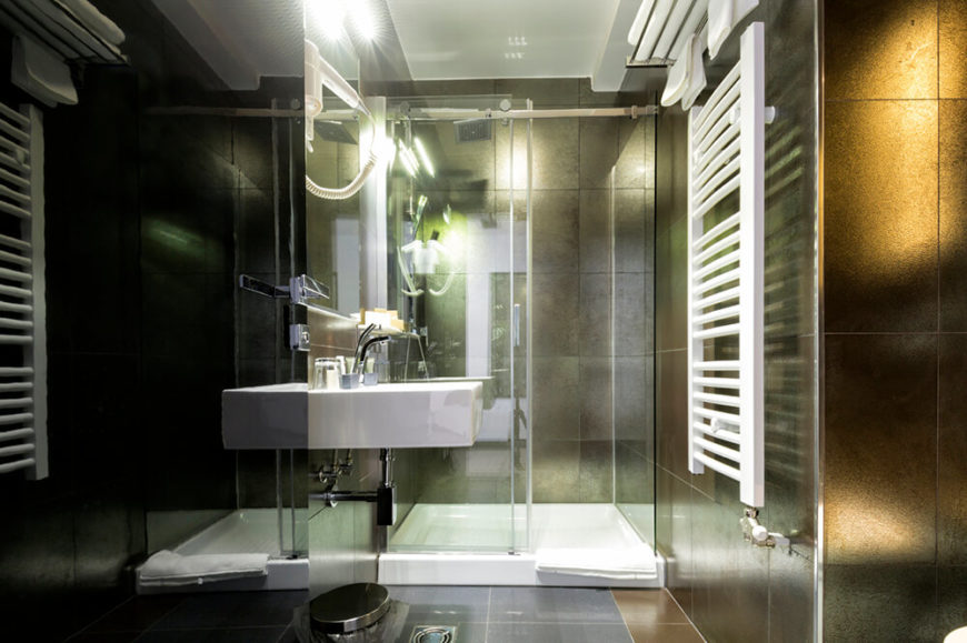 This bathroom has dark tile walls with reflective surfaces. This makes the space seem very modern. A glass walled walk in shower is featured at the far end of the room, while a floating sink is mounted on the wall to the left.
