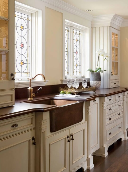 This kitchen counter is covered with dark brown countertops, contrasted by the white cabinetry and drawers. Stained glass windows above the sink and countertop match the design of the room, and add small splashes of color to the space.