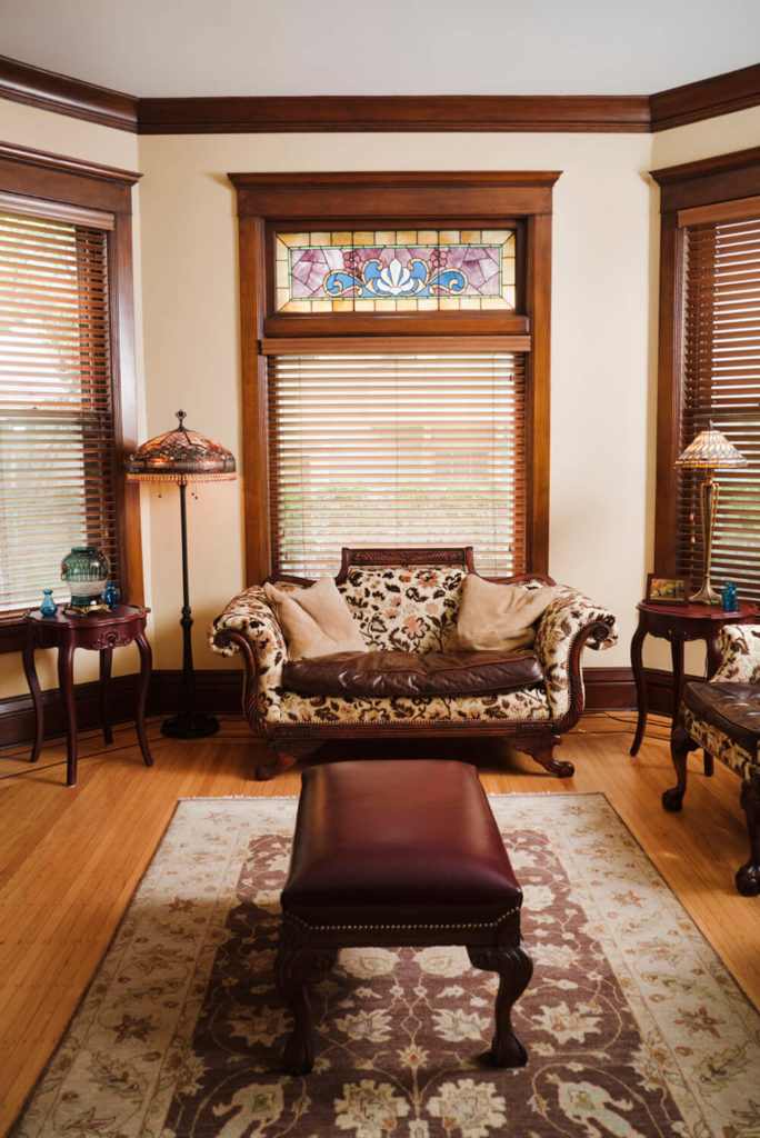 The light hardwood floors match the stained wood trim around the windows in this room. A section of stained glass above the window gives the room its character, and compliments the design on both the furniture and the area rug.