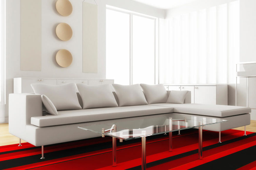 This Living Room Features A White Couch With Sharp Right Angles The Chrome Silver Table