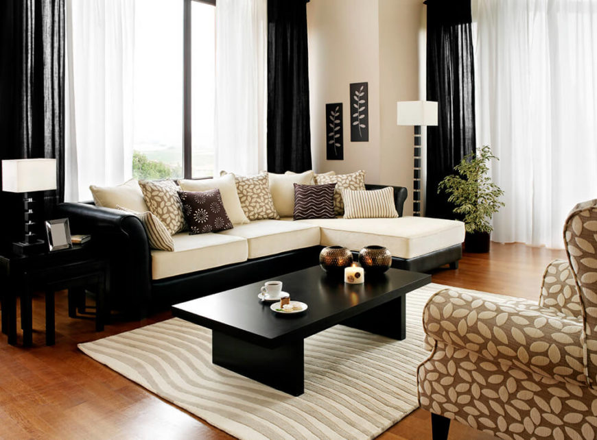 The Sleek Coffee Table Is Pitch Black, Heavily Contrasting The Area Rug And  The White