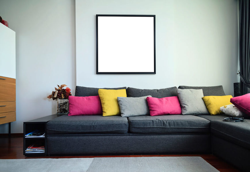 A Black Couch Holds Colorful Accent Pillows Which Provide Most Of The Color In This