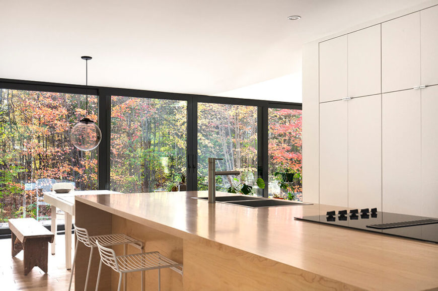 This shot from within the kitchen gives us a taste of some of the views that the homeowner will get to experience during the changing seasons. The light wood island matches that of the floor throughout the house, while an eat in extension is located near the edge of the island.