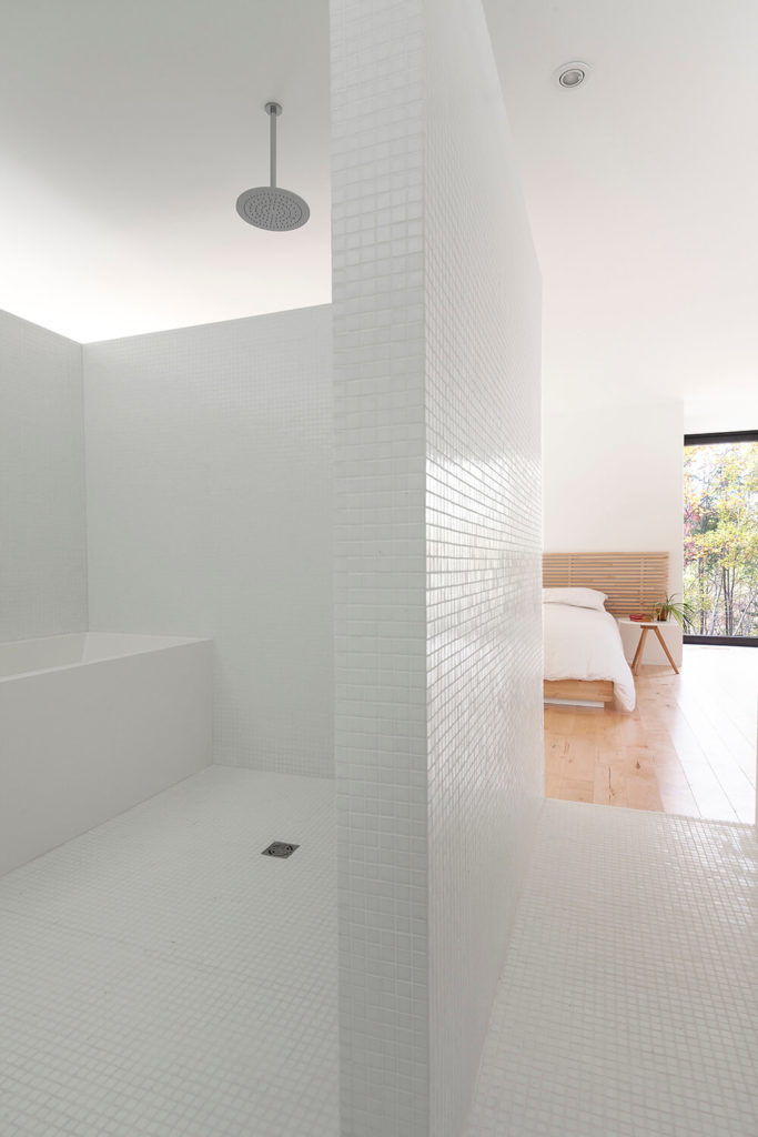 Notice that the bathroom does not have a door, so it was important to design the walls so that one could still have privacy in the bathroom. Small white square tiles cover the entire floor and walls in this space.