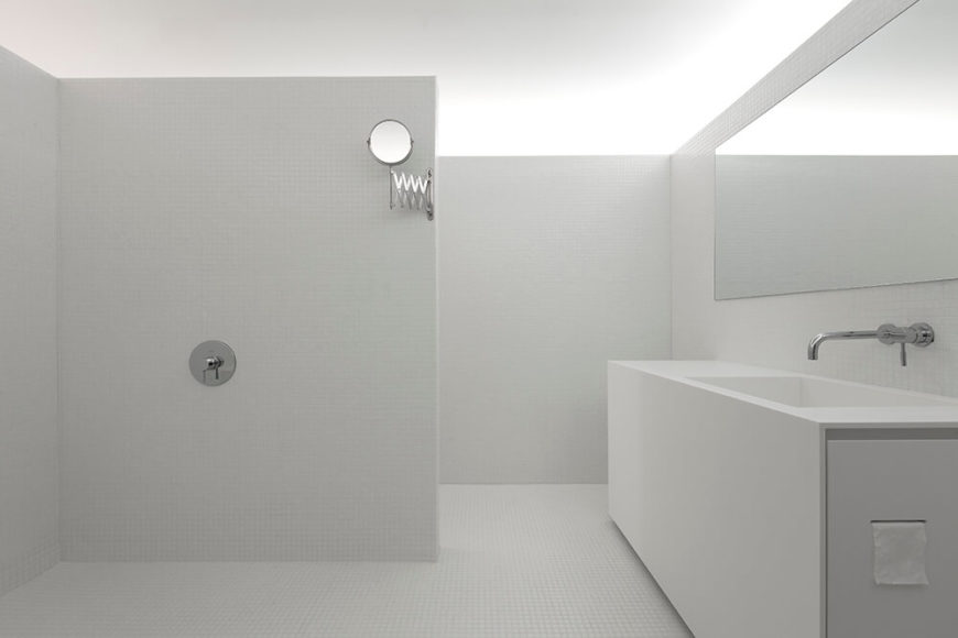 As we enter the full bathroom space, it is much larger than one might expect. This bathroom features a large sink, with an open shower area.