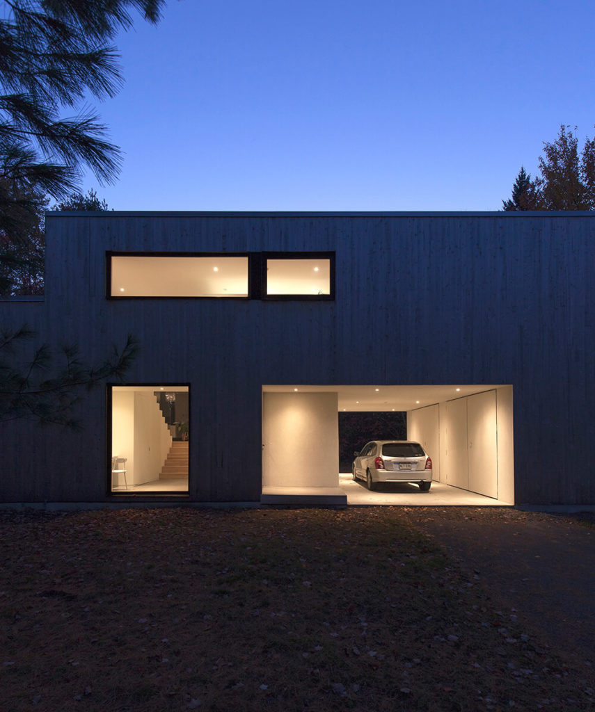 The lighting in the garage and entryway make this exterior feel welcoming even as the sun goes down. The large windows do expose parts of the interior, but they are strategically placed as not to reveal too much so that those inside will feel exposed.