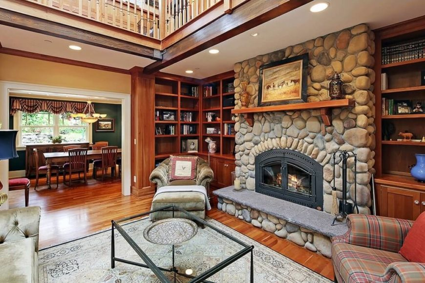 this luxurious lodge living room centers on a massive stone fireplace flanked by full height - Family Room Design Ideas