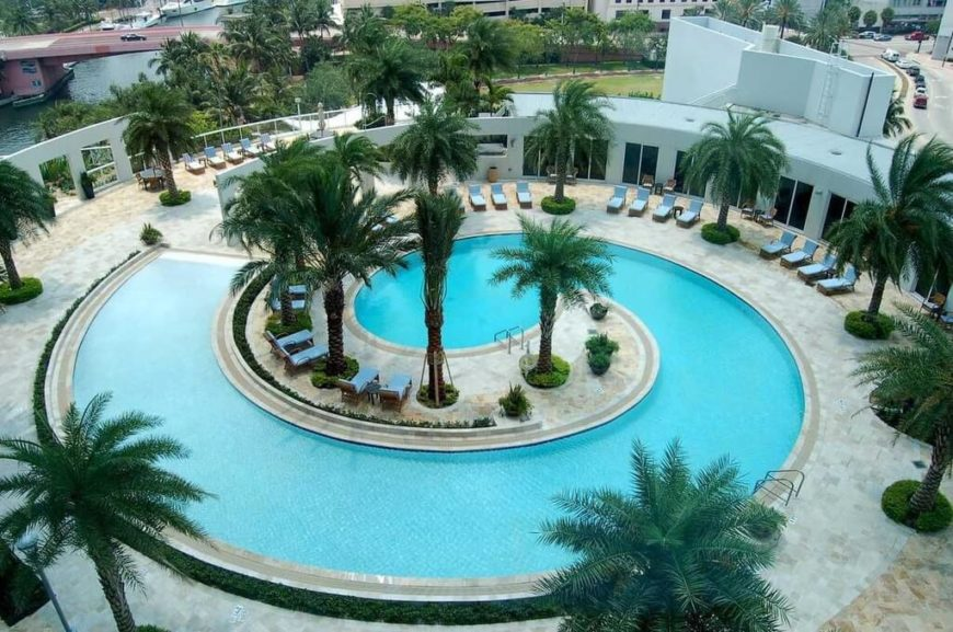 This beautiful in-ground pool is the perfect example to show that concrete pools can really be customized completely. This beautiful pool is shaped like a spiral shell, with a row of palms spiraling the opposite way.