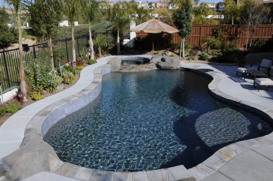 A lovely free form style pool with a small spa area on the far end and a shaded patio umbrella. The pool is concrete with natural stone tile bordering.