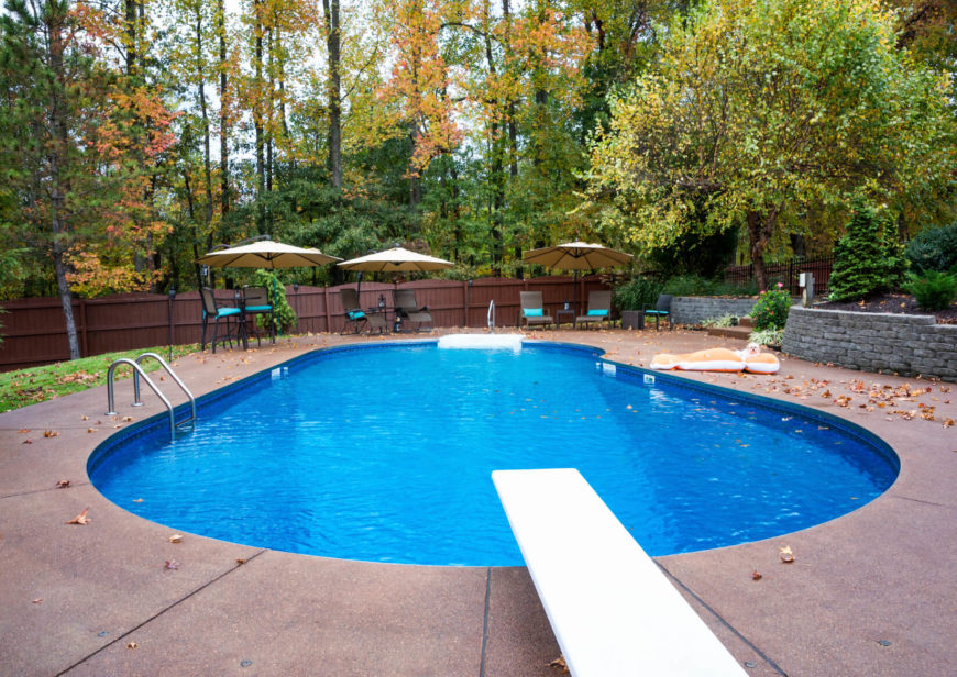 A typical swimming pool much like you'll see throughout the suburban United States. This pool features a diving board, pool ladder, and a large patio area to the rear of the lot.
