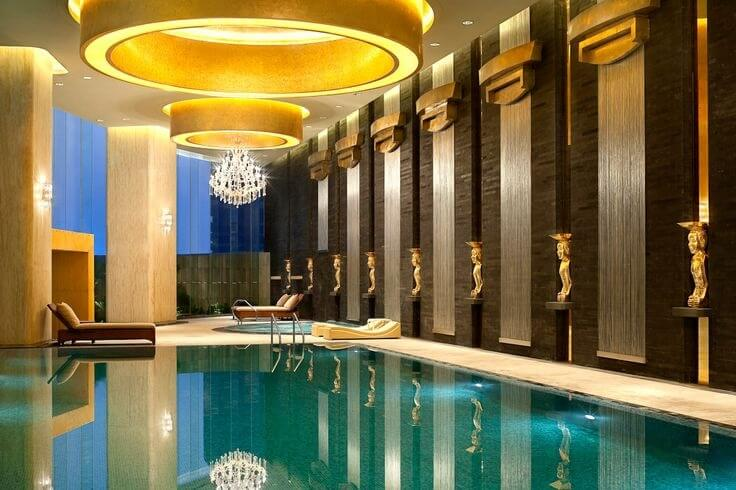 A luxurious example with gilded statuettes all along the right wall and several circular tray ceilings culminating in a chandelier above the hot tub.