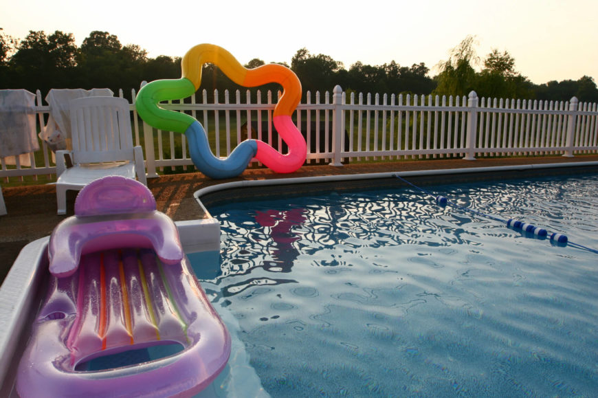 This simple backyard pool is Roman style, and is surrounded by wooden decking and a vinyl picket fence. Various inflatable toys and lounge chairs are visible.