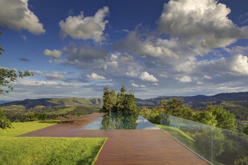 This gorgeous infinity pool seems to extend over the hill and pour over the side of the rolling hills. The edge is so smooth, it appears to simply continue on. The decking is flush with the edge of the water as well.