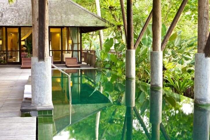 This tropical example has concrete footed beams covering the pool, reducing rainfall or vegetation that make it into the emerald waters.